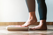 istock Female checking kilogrammes getting on the scale - self care and body positivity concept - warm flare on left 1286893989
