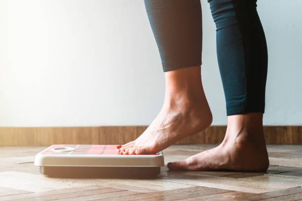 weibliche kontroll-kilogramm immer auf der waage - selbstpflege und körper positivität sytorität konzept - warme flare auf der linken seite - abnehmen stock-fotos und bilder