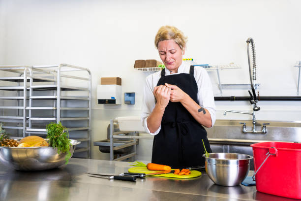 a female chef accidentally cuts her finger in a commercial kitchen while preparing food. - knife wound stock photos and pictures