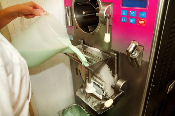 Chef feminino na fábrica de sorvete está despejando mistos ingredientes básicos, leite, mistura de sabores de menta na máquina de fazer sorvete de produção. Confeiteiro despejando base sorvete máquina de congelador. - foto de acervo