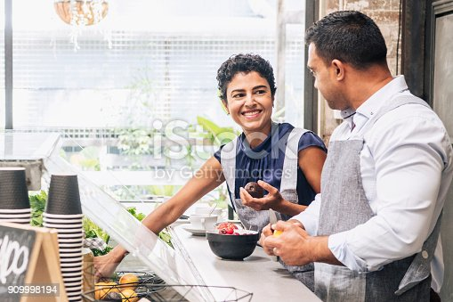 istock Female chef collecting ingredients and smiling to colleague 909998194