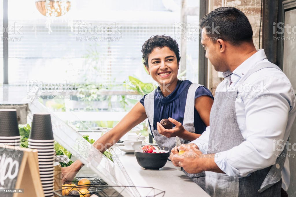 Female chef collecting ingredients and smiling to colleague stock photo