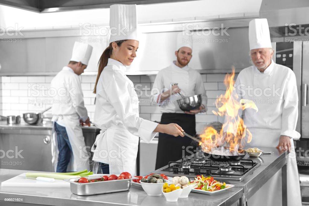 Superb Mujeres Chef Cocina Sartén En Llamas En La Cocina Foto De Stock Libre De  Derechos