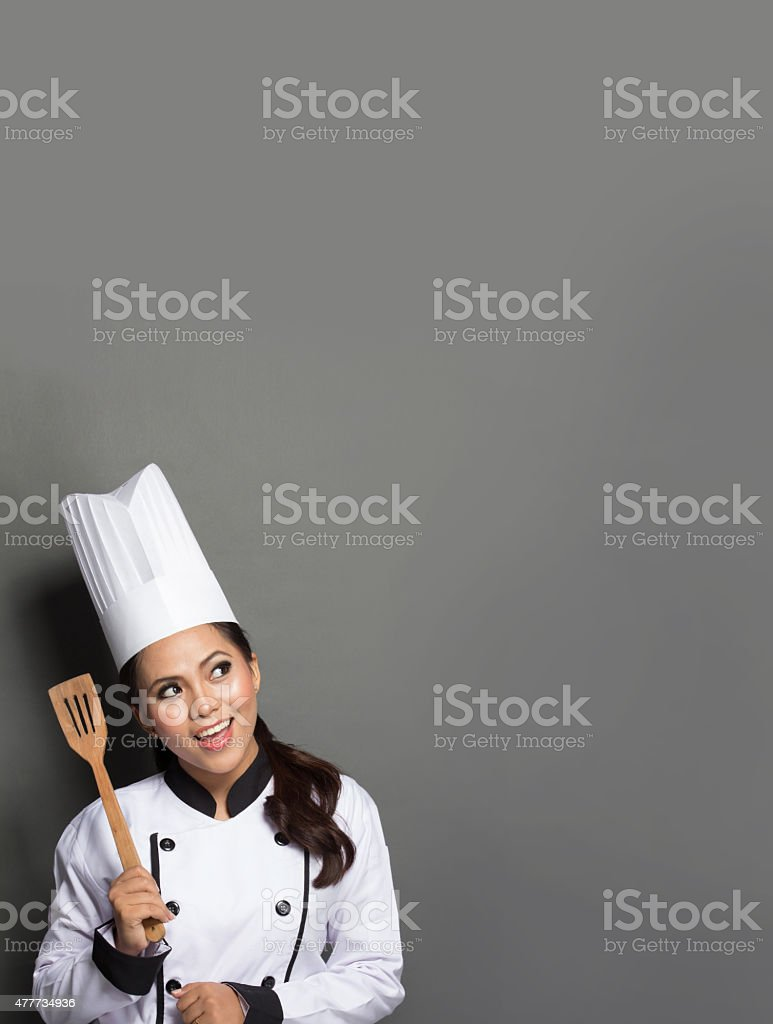 female chef cooking thinking what to cook stock photo