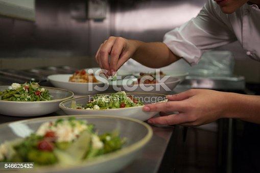istock Female chef garnishing appetizer plates at order station 846625432