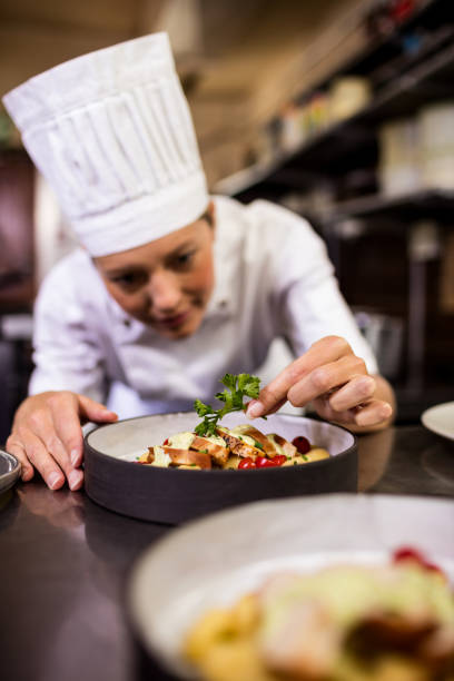 Female chef garnishing delicious desserts in a plate stock photo