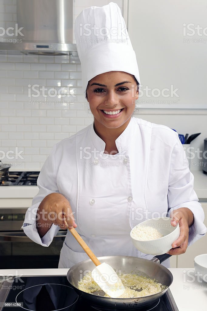 A female chef happily cooking risotto royalty-free stock photo