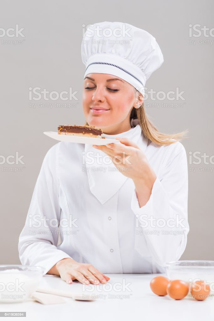 Female chef holding slice of cake stock photo