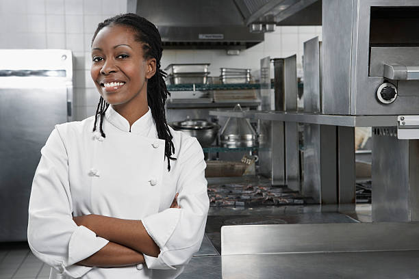Female Chef In The Kitchen Portrait of a smiling female chef with hands crossed in the kitchen chef's whites stock pictures, royalty-free photos & images