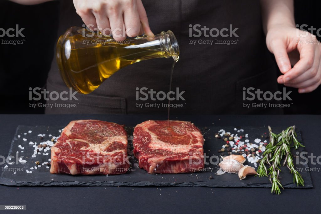 Female chef pouring olive oil, two fresh raw steak ribeye beef on a dark background. Nearby is a mixture of peppers,sea salt, garlic and rosemary royalty-free stock photo