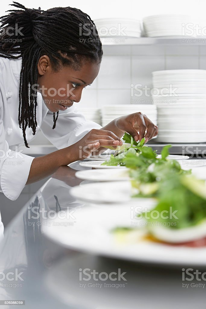 Female Chef Preparing Salad In Kitchen stock photo