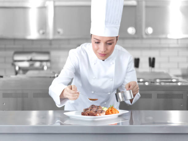 Female chef preparing steak plate stock photo