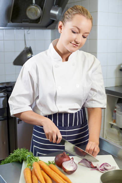 Female Chef Preparing Vegetables In Restaurant Kitchen Female Chef Preparing Vegetables In Restaurant Kitchen chef's whites stock pictures, royalty-free photos & images