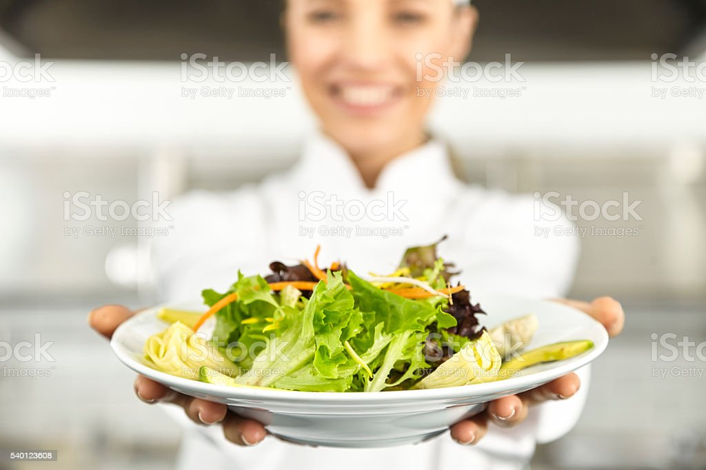 Female chef presenting salad stock photo