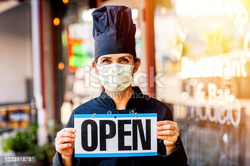 istock Female chef restaurant owner posing wearing a mask holding an Open Sign 1223918781