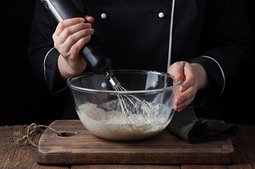 istock Female chef stirring his batter with a whisk on a black background 941225682
