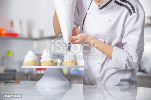 Female chef with confectionery bag squeezing cream on cupcakes.
