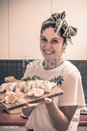 Smiling female chef with empanadas plate