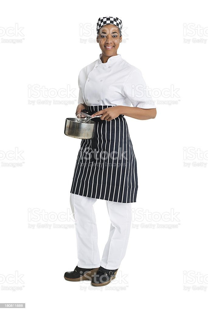 Female chef with pan and whisk on white background. stock photo