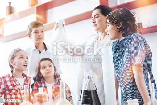 istock Female chemist showing fuming flask her little scientists 906005326