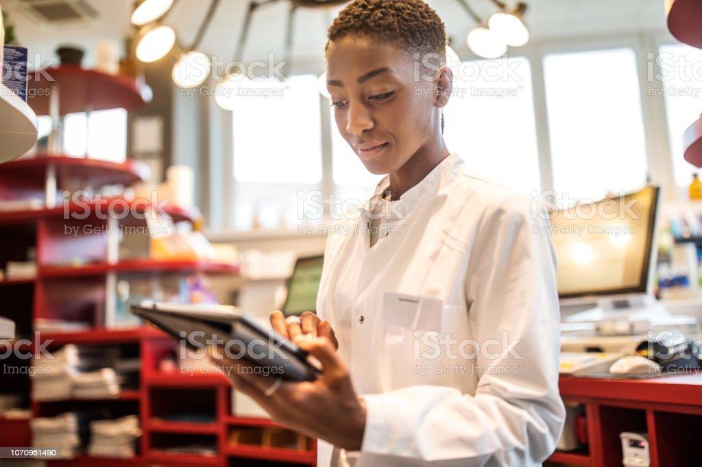 Weiblichen Chemiker mit digital-Tablette in Apotheke – Foto
