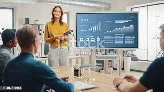 Female Chief Analyst Holds Meeting Presentation for a Team of Economists. She Shows Digital Interactive Whiteboard with Growth Analysis, Charts, Statistics and Data. People Work in Creative Office.