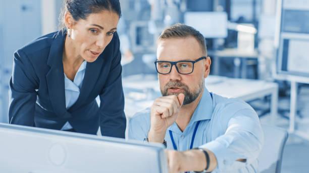 Weibliche Chefingenieurin spricht mit Elektronikspezialistin, erklärt Dinge, er arbeitet auf Desktop-Computer, sie lächeln. Modernes und helles Büro mit stilvollen Menschen – Foto