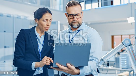 Female Chief Engineer Talks with Male Electronics Specialist, Explaining Things, He Holds on Laptop Computer. Modern and Bright Office with Stylish People and Working Robot Arm in Background