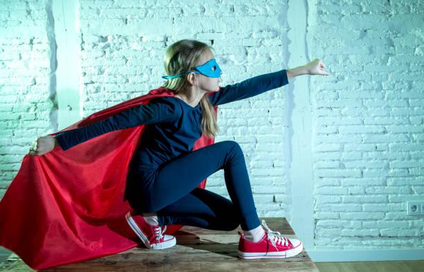flickebarn 7 eller 8 år gammal ung flicka utför glad och upprymd poserar bär mössa och mask super hjälte fantasy kostym ser lekfull i studioljus dramatiska set - superwoman barn bildbanksfoton och bilder