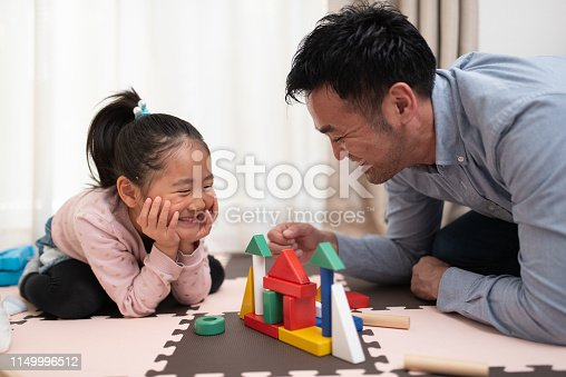 istock Female child and father playing with building blocks 1149996512
