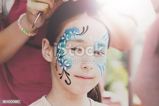 istock Female child face painting, making butterfly process 604000982