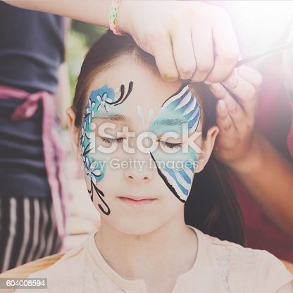 istock Female child face painting, making butterfly process 604008594