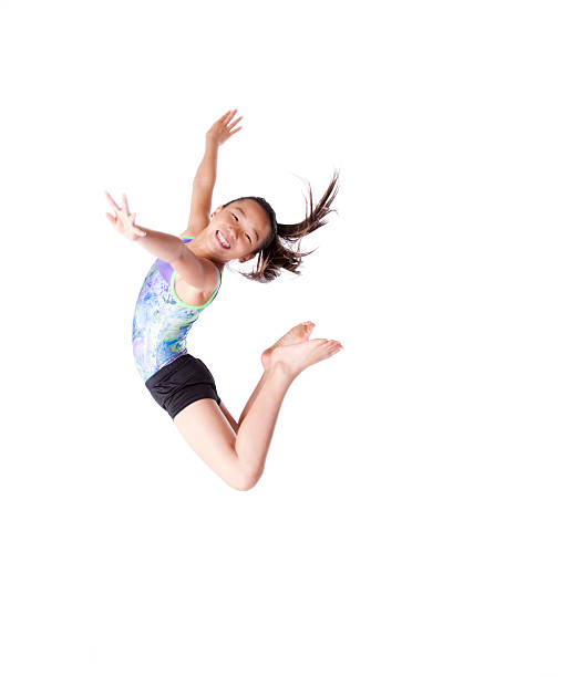 Female child gymnast jumping in the air stock photo