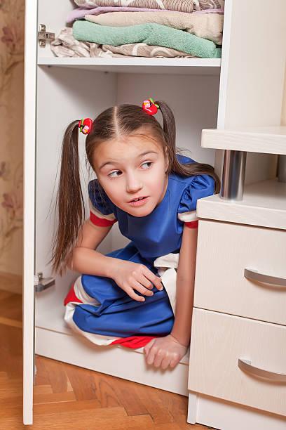 female child looks out of the closet. - jagdthema schlafzimmer stock-fotos und bilder