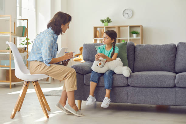 Female child psychologist working with a little preschool girl in a bright office. stock photo