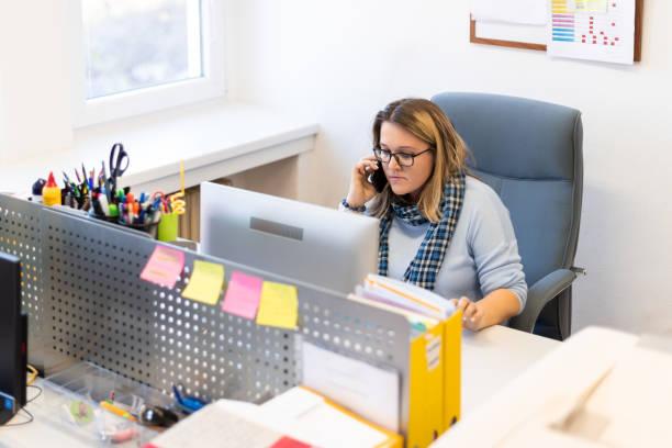Kindertherapeutin in einem Büro während eines Telefonats, mit Online-Kalender, um Patienten Termine zu vereinbaren. Kalenderplaner Organisationskonzept. – Foto