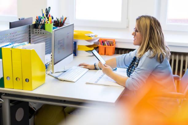 Weibliche Kindertherapeutin in einem Büro während eines Telefonats, mit Online-Kalender, um Patiententermine zu planen. Kalenderplaner Organisationsmanagementkonzept. – Foto