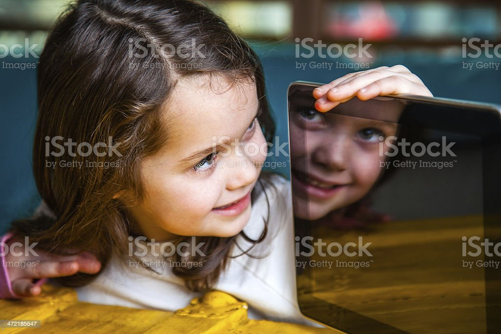 Female Child with Smiling Face Reflected in Computer Tablet royalty-free stock photo