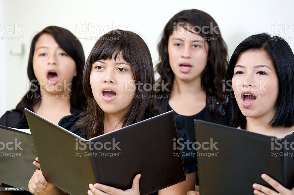 Female choir singing while holding open music books stock photo
