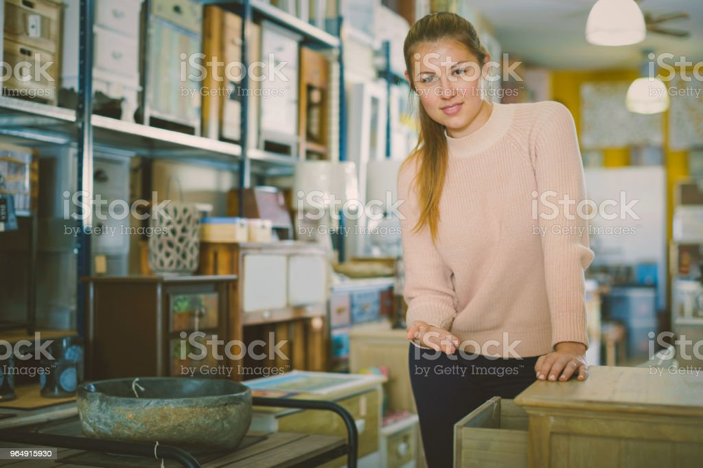 Female choosing commode in the furniture store royalty-free stock photo