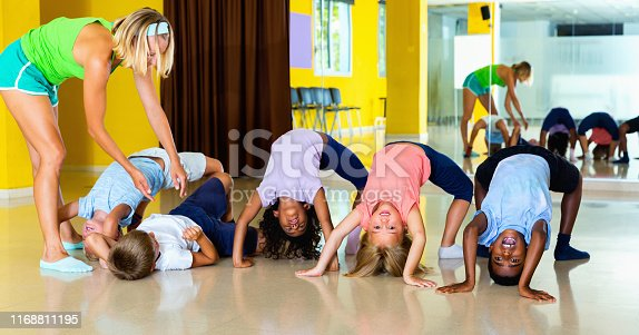 Diligent smiling positive  female choreographer helping tweenagers make gymnastic bridge in modern dance studio