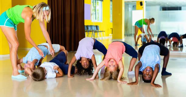 coreógrafa femenina ayudando a los tweenagers hacer puente gimnástico en el estudio de danza moderna - gimnasia fotografías e imágenes de stock