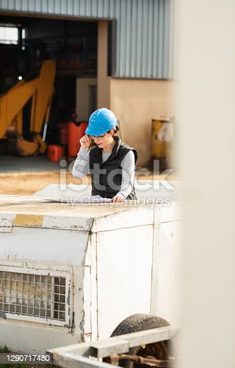 Female civil engineer in a hardhat standing outside of a warehouse and going over blueprints