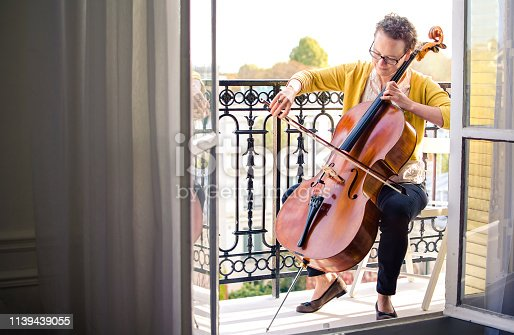 Female classical musician playing cello on a balcony in Paris