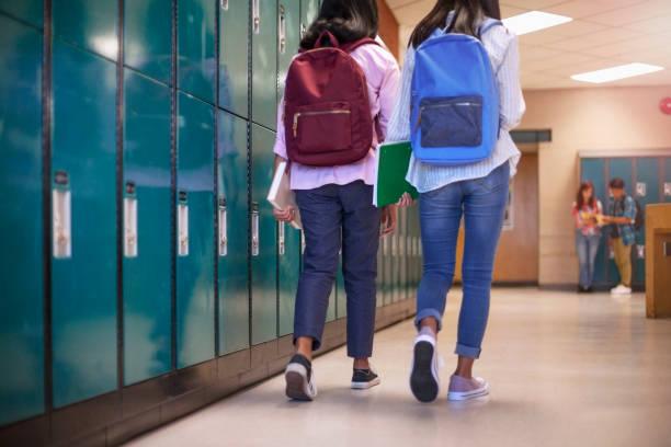 Female classmate friends with backpacks walking by lockers in school stock photo