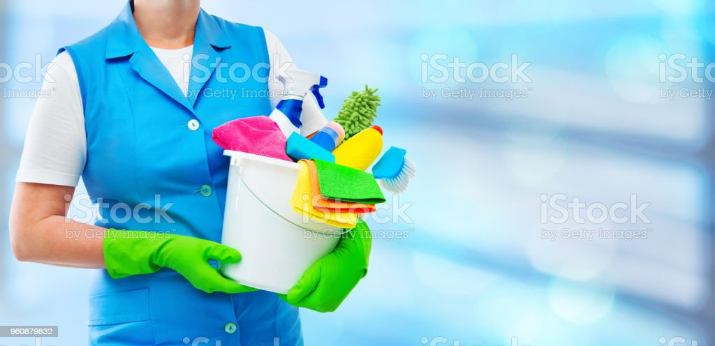 Female cleaner holding a bucket with cleaning supplies stock photo