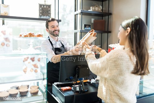 Friendly mid adult owner giving fresh bread loaves to woman in bakery shop