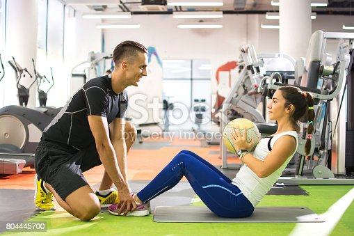 istock Female client doing abdominal crunches with ball while her personal trainer assisting her. 804445700