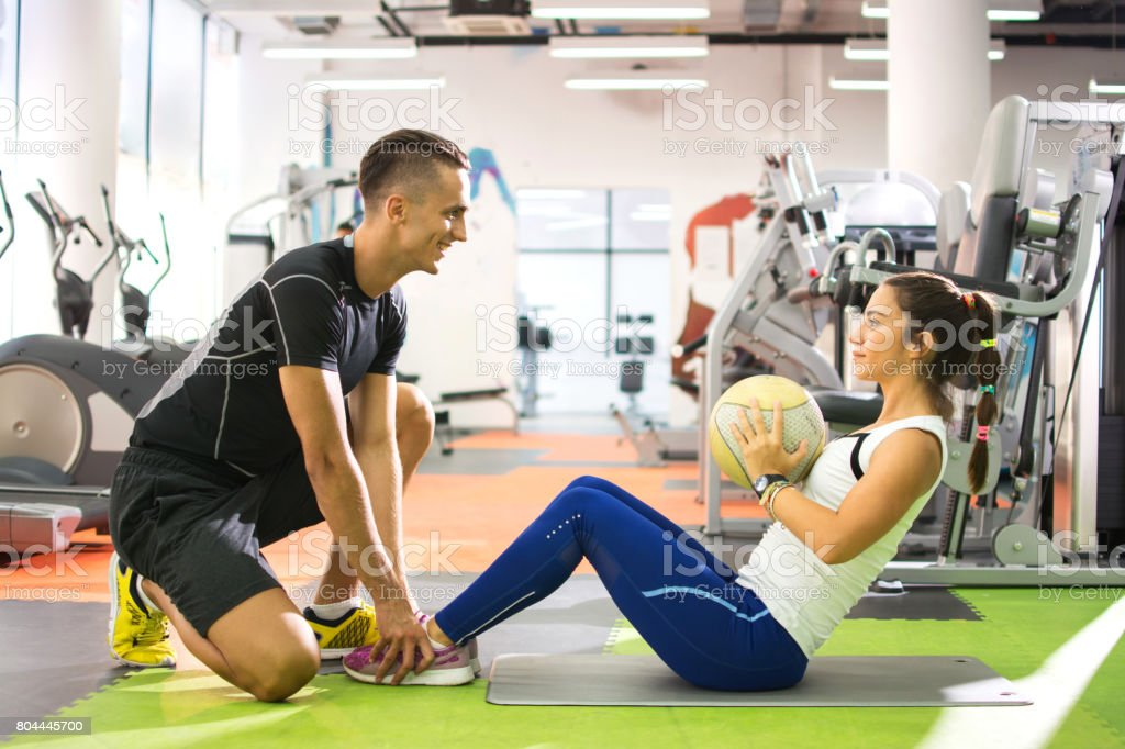 Female client doing abdominal crunches with ball while her personal trainer assisting her. - foto stock