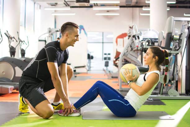 cliente mujer haciendo abdominales con la bola mientras que su entrenador personal le ayuda a. - entrenador personal fotografías e imágenes de stock